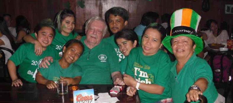 Jim Turner surrounded by midgets that made up the management and staff of the Hobbit House in Malate, Manila. Contributed Photo